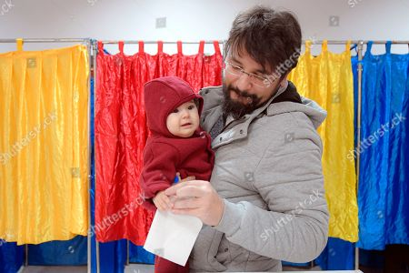 A man holds a baby as he prepares to cast his vote in Bucharest, Romania, . Romanians are voting in a presidential runoff election in which incumbent Klaus Iohannis is vying for a second term, facing Social Democratic Party leader Viorica Dancila, a former prime minister, in Sunday's vote