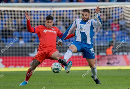 Getafe's Mathias Olivera, left, challenges with Espanyol's David Lopez, during the Spanish La Liga soccer match between Espanyol and Getafe at the RCDE Stadium in Barcelona, Spain