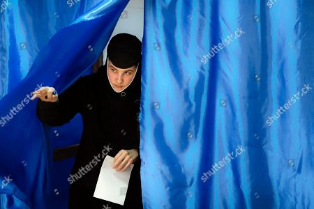 An Orthodox nun exits a voting cabin in Pasarea, Romania, . Romanians are voting in a presidential runoff election in which incumbent Klaus Iohannis is vying for a second term, facing Social Democratic Party leader Viorica Dancila, a former prime minister, in Sunday's vote