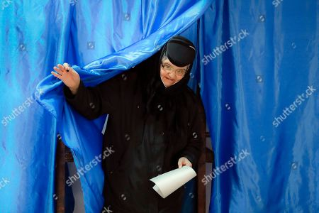 Stock Picture of An Orthodox nun exits a voting cabin in Pasarea, Romania, . Romanians are voting in a presidential runoff election in which incumbent Klaus Iohannis is vying for a second term, facing Social Democratic Party leader Viorica Dancila, a former prime minister, in Sunday's vote