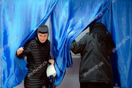 Stock Photo of An Orthodox nun exits a voting cabin in Pasarea, Romania, . Romanians are voting in a presidential runoff election in which incumbent Klaus Iohannis is vying for a second term, facing Social Democratic Party leader Viorica Dancila, a former prime minister, in Sunday's vote