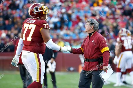 Washington Redskins head coach Bill Callahan, right, talks with offensive guard Ereck Flowers (77) during the first half of an NFL football game against the Detroit Lions, in Landover, Md