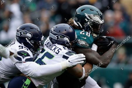Philadelphia Eagles' Jay Ajayi (28) is tackled by Seattle Seahawks' Mychal Kendricks (56) and L.J. Collier (95) during the first half of an NFL football game, in Philadelphia