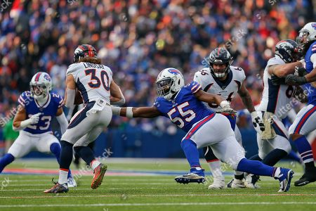Stock Image of Buffalo Bills defensive end Jerry Hughes (55) reaches for Denver Broncos running back Phillip Lindsay (30) during the second quarter of an NFL football game, in Orchard Park, N.Y