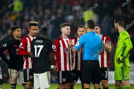 Sheffield United and Manchester United argue with Referee Andre Marriner as Oliver McBurnie of Sheffield United's goal is reviewed by VAR