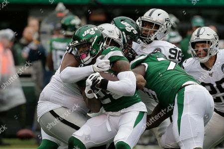 New York Jets running back Le'Veon Bell is tackled by Oakland Raiders' Johnathan Hankins, left, during the first half of an NFL football game, in East Rutherford, N.J