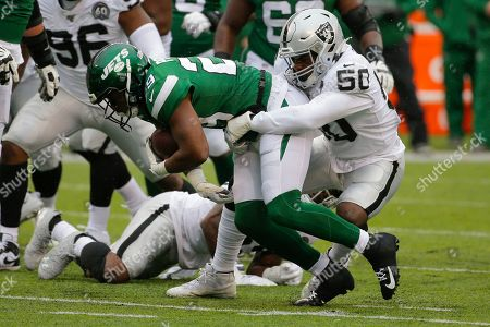Oakland Raiders' Nicholas Morrow (50) tackles New York Jets' Bilal Powell (29) during the first half of an NFL football game, in East Rutherford, N.J