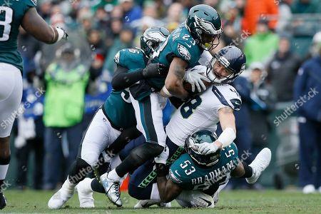 Seattle Seahawks' Jacob Hollister (48) is tackled by Philadelphia Eagles' Nigel Bradham (53), Rodney McLeod (23) and Derek Barnett (96) during the first half of an NFL football game, in Philadelphia
