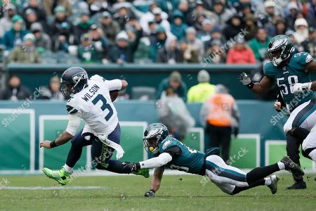 Seattle Seahawks' Russell Wilson, left, tries to avoid Philadelphia Eagles' Rodney McLeod during the first half of an NFL football game, in Philadelphia