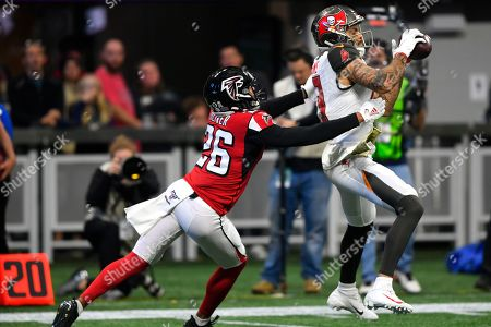 Tampa Bay Buccaneers wide receiver Mike Evans (13) makes the catch against Atlanta Falcons cornerback Isaiah Oliver (26) during the first half of an NFL football game, in Atlanta