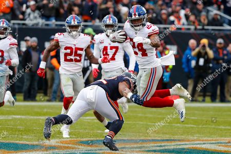 David Montgomery, Julian Love. New York Giants cornerback Julian Love (24) is tacked by Chicago Bears running back David Montgomery (32) after an interception during the second half of an NFL football game in Chicago