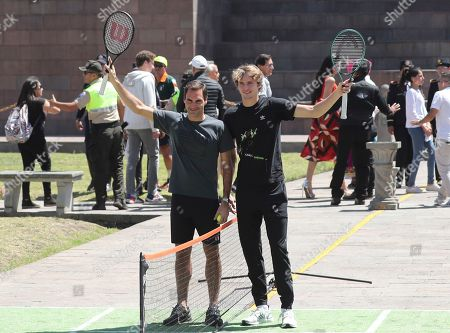 Swiss Roger Federer, left, and German Alexander Zverev pose for a photo at Mitad del Mundo on the equator in Quito, Ecuador. . Federer and Zverev will hold an exhibition game tonight. For Federer this will be his first time in Ecuador