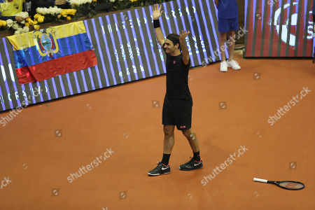 Roger Federer throws his arms up after missing a point during an exhibition game with Alexander Zverev at Rumiñahui Coliseum in Quito, Ecuador
