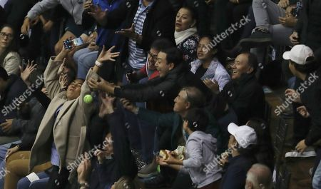 Fans scramble to catch a tennis ball thrown by Roger Federer during an exhibition game with Alexander Zverev at Rumiñahui Coliseum in Quito, Ecuador
