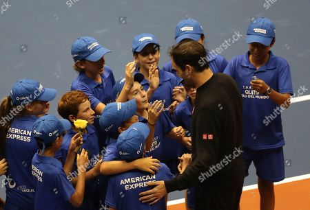 Ball boys and girls mob Roger Federer during an exhibition game with Alexander Zverev at Rumiñahui Coliseum in Quito, Ecuador
