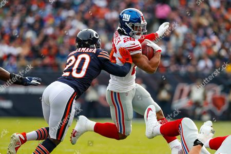New York Giants running back Saquon Barkley (26) is hit by Chicago Bears cornerback Prince Amukamara (20) during the first half of an NFL football game in Chicago