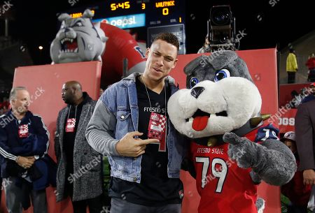 Aaron Judge, Timeout. Former Fresno State baseball player and now New Yankee outfielder, Aaron Judge, hangs out with mascot Timeout as the Bulldogs take on Nevada during the first half of an NCAA college football game in Fresno, Calif