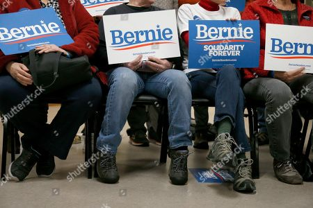 Supporters of Democratic presidential candidate Sen. Bernie Sanders, I-Vt., hold signs in their laps before Sanders arrived at a campaign stop, in Hillsboro, N.H