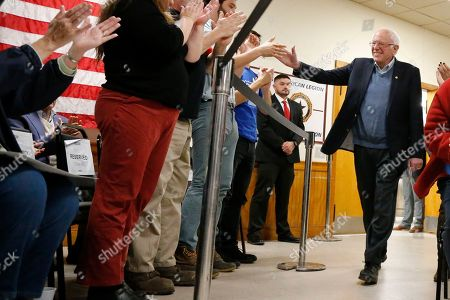 Democratic presidential candidate Sen. Bernie Sanders, I-Vt., high-fives supporters as he arrives at a campaign stop, in Hillsboro, N.H
