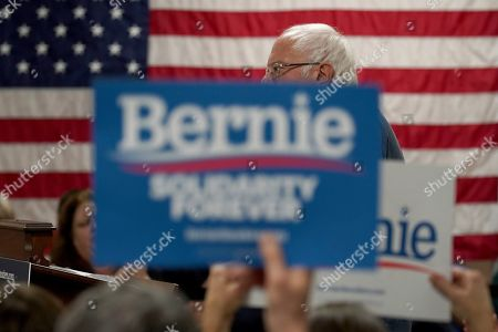 As campaign signs block his face, Democratic presidential candidate Sen. Bernie Sanders, I-Vt., speaks during a campaign stop, in Hillsboro, N.H