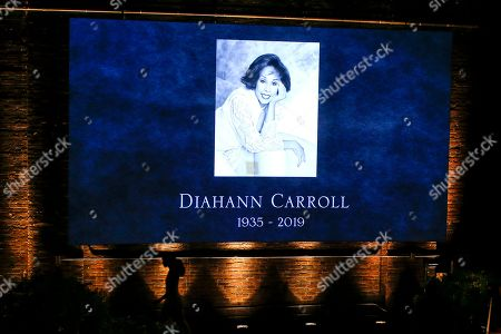 A woman walks next to a projection of late actress Diahann Carroll during her memorial at the Helen Hayes Theater on in New York