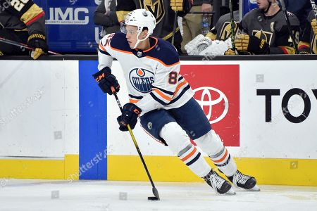 Edmonton Oilers defenseman Caleb Jones skates with the puck against the Vegas Golden Knights during the second period of an NHL hockey game, in Las Vegas