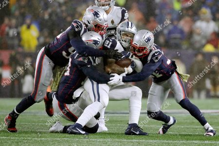 Stock Image of New England Patriots defenders Jamie Collins, left, Kyle Van Noy and Jonathan Jones, right, tackle Dallas Cowboys running back Ezekiel Elliott in the first half of an NFL football game, in Foxborough, Mass
