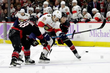 Florida Panthers' Brian Boyle (9) battles Carolina Hurricanes' Jordan Martinook (48) and Brett Pesce (22) for the puck during the first period of an NHL hockey game in Raleigh, N.C