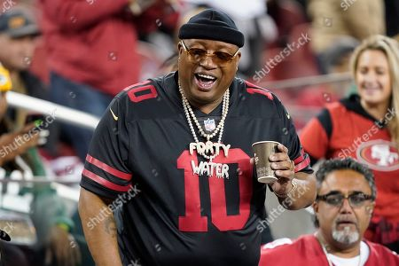 Stock Image of Rapper E-40 smiles during the second half of an NFL football game between the San Francisco 49ers and the Green Bay Packers in Santa Clara, Calif