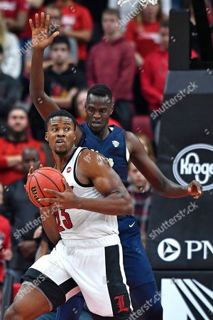 Louisville center Steven Enoch (23) looks for help from the defense of Akron forward Xeyrius Williams (20) during the first half of an NCAA college basketball game in Louisville, Ky
