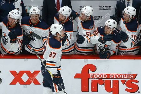 Edmonton Oilers center Connor McDavid (97) celebrates his goal against the Arizona Coyotes with Oilers' Ethan Bear (74), Caleb Jones (82), Adam Larsson (6), Patrick Russell (52), Gaetan Haas (91) and Joakim Nygard (10) during the shootout of an NHL hockey game, in Glendale, Ariz. The Oilers defeated the Coyotes 4-3