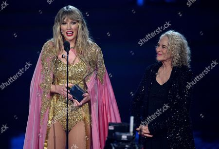 Taylor Swift, Carole King. Taylor Swift, left, accepts the award for artist of the decade at the American Music Awards, at the Microsoft Theater in Los Angeles. Looking on at right is Carole King