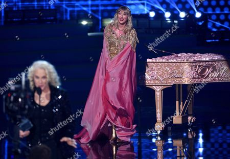 Carole King, Taylor Swift. Taylor Swift, background, looks on as Carole King introduces the award for artist of the decade at the American Music Awards, at the Microsoft Theater in Los Angeles
