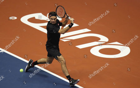 Roger Federer hits the ball during an exhibition game with Alexander Zverev at Rumiñahui Coliseum in Quito, Ecuador