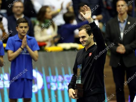 Roger Federer of Switzerland waves while holding a trophy after winning an exhibition match against Alexander Zverev of Germany, at the Ruminahui Coliseum in Quito, Ecuador, 24 November 2019.