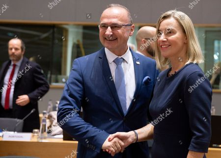 European Union foreign policy chief Federica Mogherini, right, shakes hands with Croatia's Minister for Development Gordan Grlic Radman during a meeting of EU foreign ministers at the EU Council building in Brussels