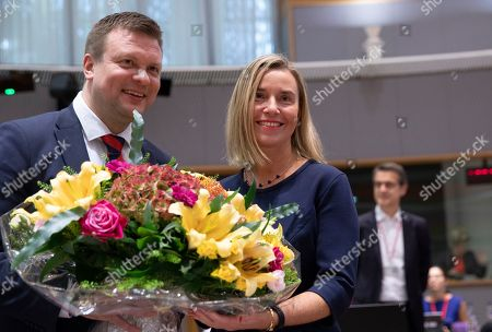 European Union foreign policy chief Federica Mogherini, right, receives a flower bouquet from Finnish Minister for Development Cooperation and Foreign Trade Ville Skinnari during a meeting of EU foreign ministers at the EU Council building in Brussels