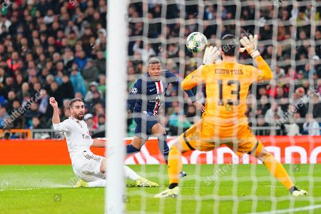 Goalkeeper Thibaut Courtois of Real Madrid saves from Kylian Mbappé of Paris Saint-Germain