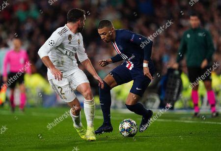 Kylian Mbappé of Paris Saint-Germain controls the ball around Dani Carvajal of Real Madrid