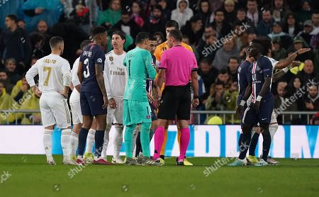 The players gather around Referee Artur Manuel Soares Dias after he presents Goalkeeper Thibaut Courtois of Real Madrid a red card in the first half. The red card is subsequently overturned following a VAR check