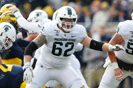 Stock Image of Michigan State offensive lineman Luke Campbell (62) blocks against Michigan in the second half of an NCAA college football game in Ann Arbor, Mich