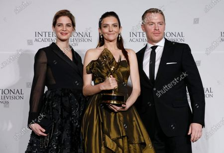 Hungarian actress Marina Gera (C) poses with German actress Rike Schmid (L) and Canadian actor Diego Klattenhoff (R) with the award in the Best Performance by an Actress category for her role in Orok Tel (Eternal Winter) the at the 47th International Emmy Awards Gala at the New York Hilton hotel in New York, USA, 25 November 2019.