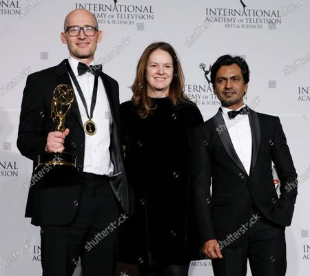 James Watkins (L), producer Dixie Linder (C) and Indian actor Nawazuddin Siddiqui (R) pose with the International Emmy award in the Drama Series category for McMafia during the New York Hilton hotel in New York, New York, USA, 25 November 2019.