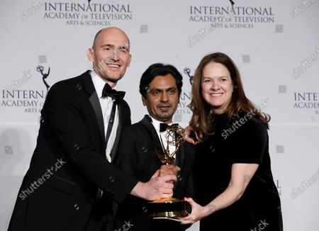 Stock Photo of James Watkins (L), producer Dixie Linder (R) and Indian actor Nawazuddin Siddiqui (C) pose with the International Emmy award in the Drama Series category for McMafia during the New York Hilton hotel in New York, New York, USA, 25 November 2019.