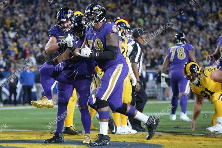 From left, Baltimore Ravens offensive guard Bradley Bozeman, running back Mark Ingram, and offensive tackle Ronnie Stanley celebrate Ingram's touchdown in an NFL football game against the Los Angeles Rams, in Los Angeles