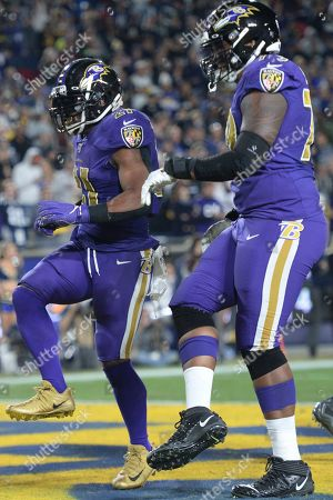 Baltimore Ravens running back Mark Ingram, left, and offensive tackle Ronnie Stanley celebrate Ingram's touchdown in an NFL football game against the Los Angeles Rams, in Los Angeles