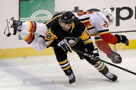 Pittsburgh Penguins' Dominik Simon (12) collides with Calgary Flames' Michael Stone (26) during the first period of an NHL hockey game in Pittsburgh