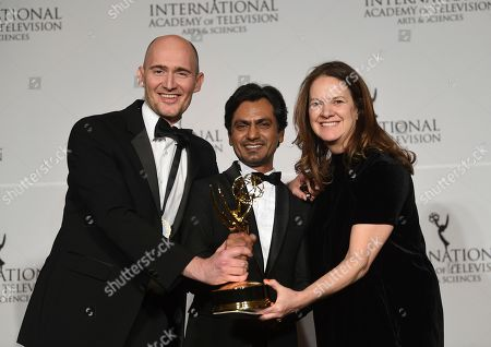 "James Watkins, Nawazuddin Siddiqui, Dixie Linder. Executive producer/director/writer James Watkins, left, actor Nawazuddin Siddiqui and executive producer Dixie Linder pose with the best drama series award for ""McMafia,"" during the 47th International Emmy Awards gala at the Hilton New York, in New York"