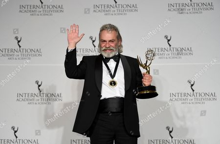 "Haluk Bilginer poses with the award for best performance by an actor for his role in ""Sahsiyet"" (Persona) during the 47th International Emmy Awards gala at the Hilton New York, in New York"
