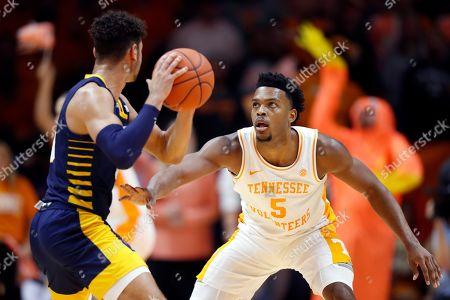 Tennessee guard Josiah-Jordan James (5) defends against Chattanooga guard Jonathan Scott (1) during the first half of an NCAA college basketball game, in Knoxville, Tenn